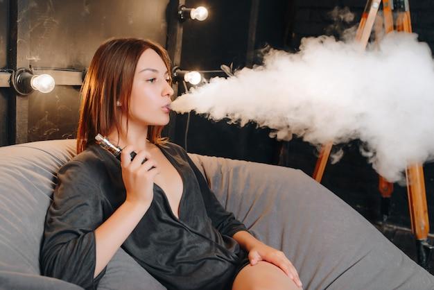 Linda garota atraente exalando vapor enquanto fuma um cigarro eletrônico, passando o tempo de lazer enquanto descansa no pufe macio sentado na sala de design.