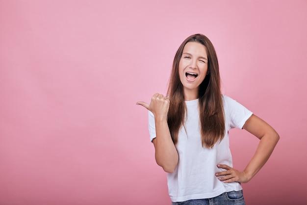 Linda garota atraente legal com camiseta mostra o polegar para o lado