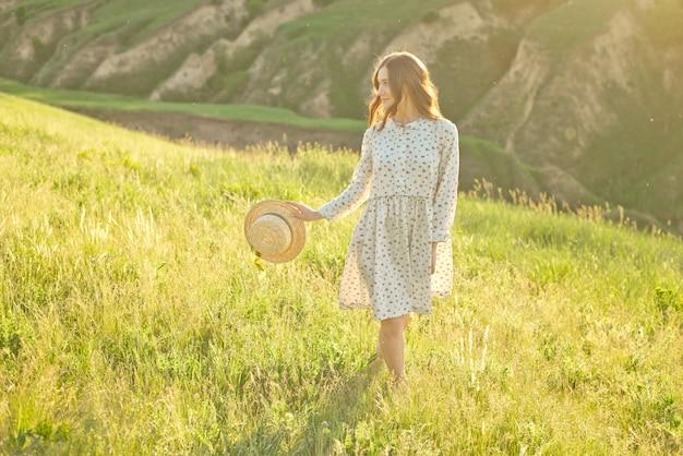 Linda garota atravessa as montanhas em suas mãos, segurando um chapéu de palha, apreciando os raios do pôr do sol.