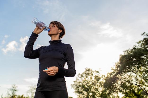 Linda garota bebendo água de uma garrafa no parque. Foto gratuita