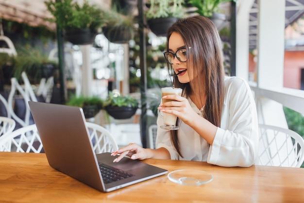 Linda garota bebendo café com leite no café num dia de verão