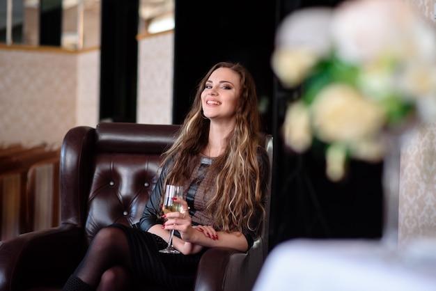 Linda garota bebendo champanhe no restaurante