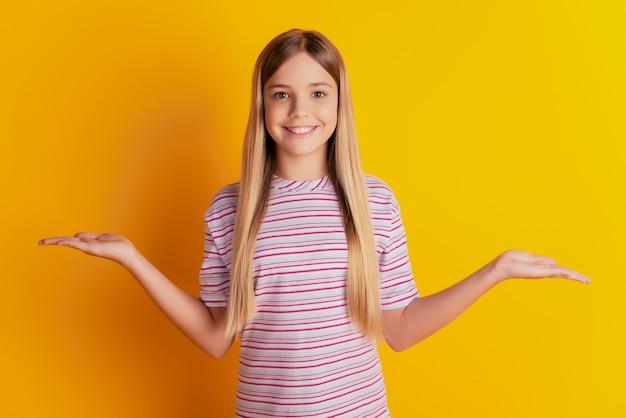 Linda garota boa amigável alegre mostrando as duas mãos e escolha em fundo amarelo