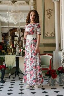 Linda garota bonita bainha vestido de cocktail com flores posando no interior da biblioteca de luxo. retrato da moda jovem modelo feminina