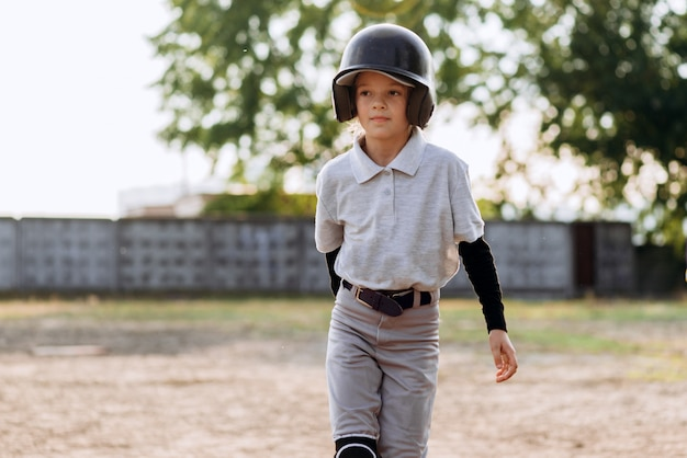 Linda garota bonita em um capacete, uniforme de beisebol joga beisebol
