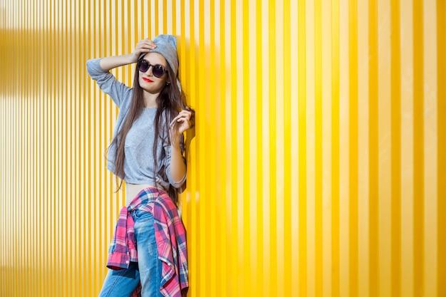 Linda garota bool sobre parede amarela