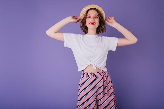 Linda garota branca com tatuagem posando com um lindo sorriso. foto interna de feliz incrível senhora usa chapéu de palha.