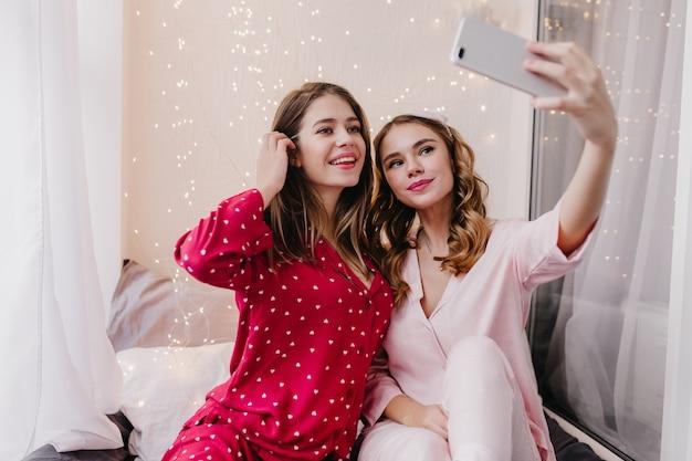 Linda garota branca posando com prazer de manhã cedo no quarto dela. mulher bonita e encaracolada usando telefone para selfie com a irmã de cabelos compridos.