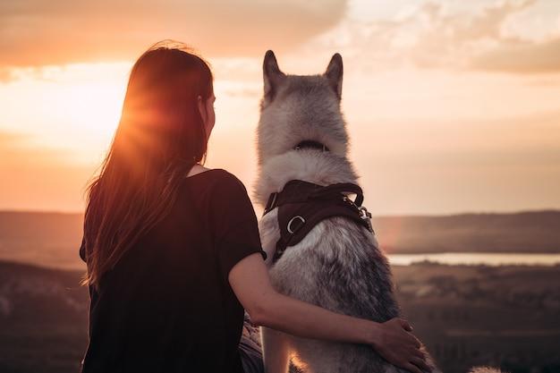 Linda garota brinca com cachorro ao pôr do sol