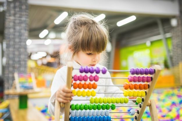 Linda garota brinca com entusiasmo com um brinquedo de madeira em desenvolvimento em uma grande sala de jogos