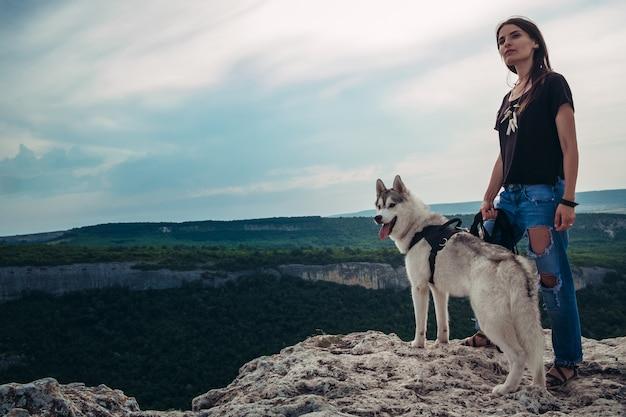 Linda garota brinca com um cão husky cinza e branco nas montanhas ao pôr do sol