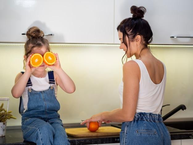 Linda garota brincando com a mãe na cozinha