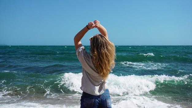 Linda garota bronzeada e de estilo boêmio na praia com as ondas do mar como pano de fundo