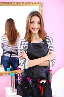 Linda garota cabeleireira em salão de beleza