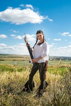 Linda garota caçadora atirando arco e flecha na pastagem