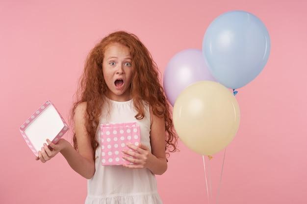 Linda garota cacheada com cabelo comprido e cacheado, animada, olhando para a câmera com a boca bem aberta, sendo surpreendida ao receber um presente de aniversário, em pé sobre um fundo rosa de estúdio com roupas festivas