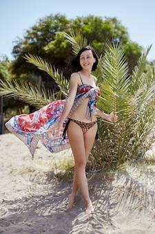 Linda garota caminha ao longo da praia em um dia ensolarado. mulher sexy esguia descansando no mar