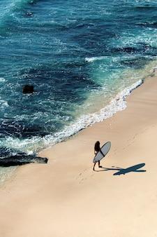 Linda garota caminha com uma prancha de surf em uma praia selvagem. vista incrível do topo.