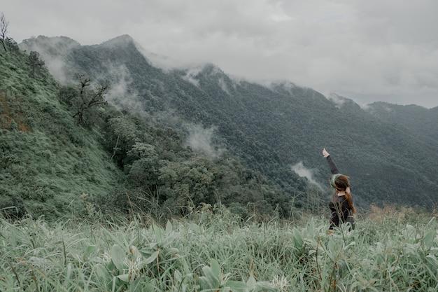 Linda garota caminhadas aventura na alta montanha com belas vistas da névoa.