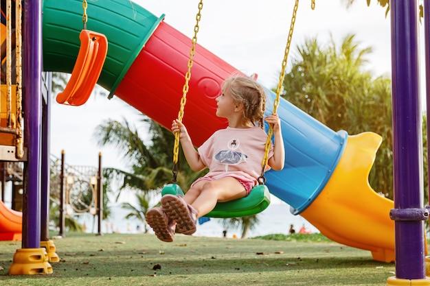 Linda garota caminhando ao ar livre no playground no verão