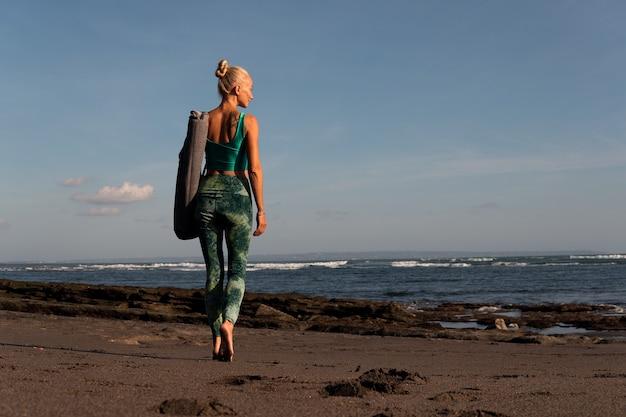 Linda garota caminhando na praia com tapete de ioga