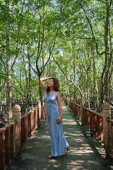 Linda garota caminhando pela floresta de mangue na ásia.