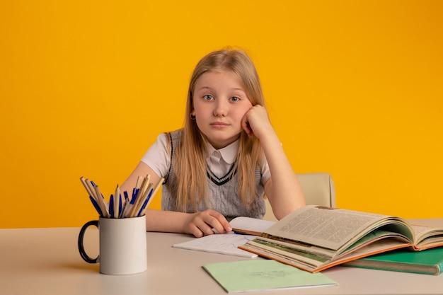 Linda garota cansada na mesa fazendo lição de casa.