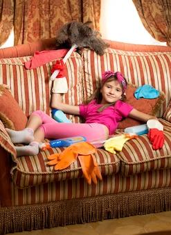 Linda garota cansada relaxando no sofá após limpar a casa