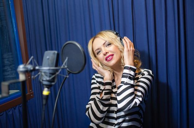 Linda garota cantando em um estúdio de gravação