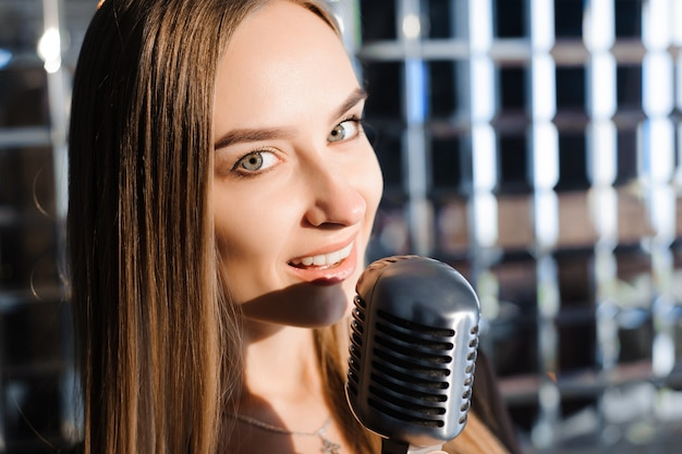 Linda garota cantando. mulher de beleza com microfone.