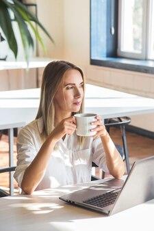 Linda garota caucasiana bebe café e trabalha em um laptop remotamente em um espaço brilhante com plantas verdes.