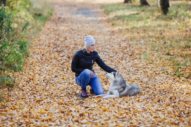Linda garota caucasiana brinca com cachorro husky na floresta de outono ou parque