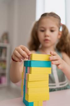 Linda garota caucasiana, brincar com os blocos de madeira multi-coloridas
