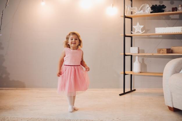 Linda garota caucasiana com cabelo curto loiro ondulado em um lindo vestido rosa sorrindo em clima de natal