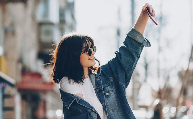 Linda garota caucasiana com cabelo preto sorrindo e olhando através dos óculos enquanto faz uma selfie no meio da cidade