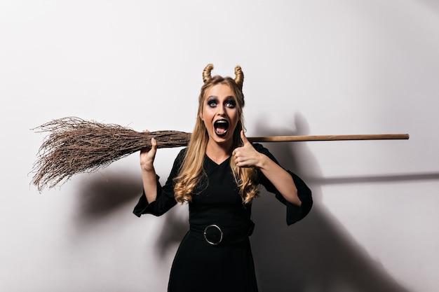 Linda garota caucasiana com fantasia de bruxa senhora bem-aventurada surpresa, relaxando na festa de halloween.
