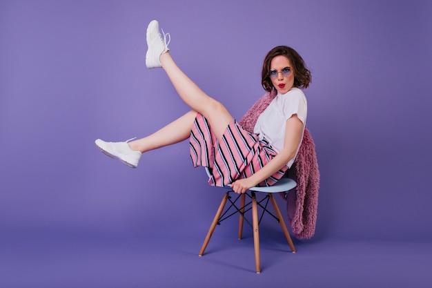 Linda garota caucasiana com maquiagem brilhante, sentada na cadeira. modelo feminino relaxado em sapatos brancos, posando na parede roxa e agitando as pernas.