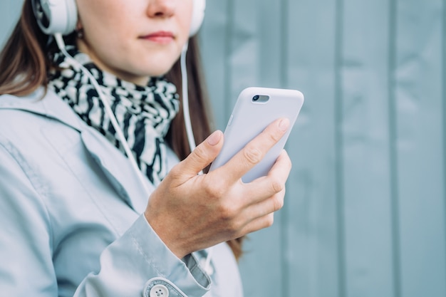 Linda garota caucasiana com um casaco cinza está falando no viva-voz em fones de ouvido via smartphone