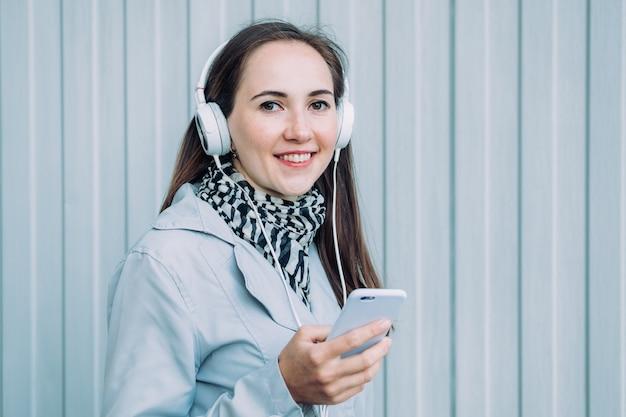 Linda garota caucasiana com um casaco cinza ouve música em fones de ouvido através de um smartphone