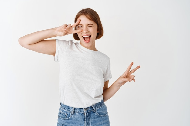 Linda garota caucasiana com um sorriso sincero, mostrando o sinal-v sobre o piscar de um olho e parecendo alegre, em pé de jeans e camiseta contra a parede branca