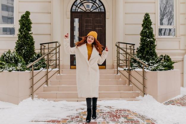 Linda garota caucasiana dançando na manhã de inverno. retrato ao ar livre da alegre mulher ruiva usa chapéu e casaco.