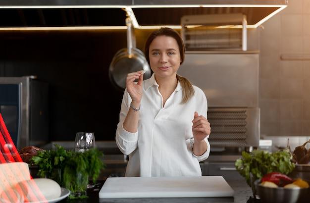 Linda garota caucasiana de pé na cozinha em um uniforme branco, sorrindo e degustando um pedaço de queijo. mulher bonita 30 anos de idade em camisa branca com vegetais de carne de queijo de ingredientes de alimentos.
