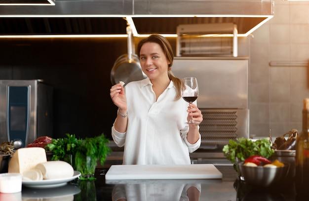 Linda garota caucasiana de pé na cozinha em um uniforme branco sorrindo e degustando vinho tinto mulher bonita 30 anos em uma camisa branca com comida ingredientes queijo carne vegetais bebendo