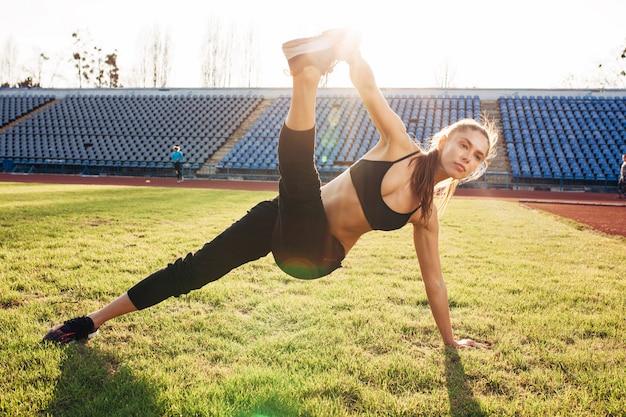 Linda garota caucasiana esportiva fazendo exercícios ao ar livre.