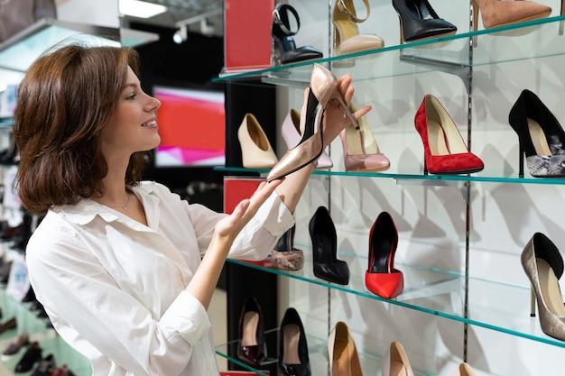 Linda garota caucasiana parece sapatos brilhantes em um grande shopping
