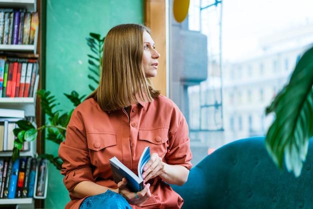 Linda garota caucasiana passa seu tempo livre em casa sentado no sofá, lendo um livro e olhando para o ...