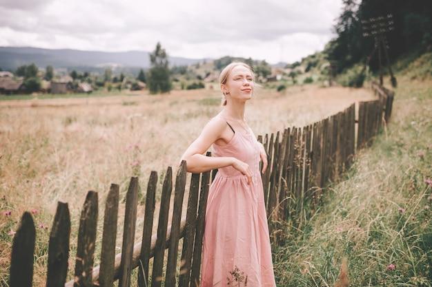 Linda garota caucasiana posando perto de cerca de madeira