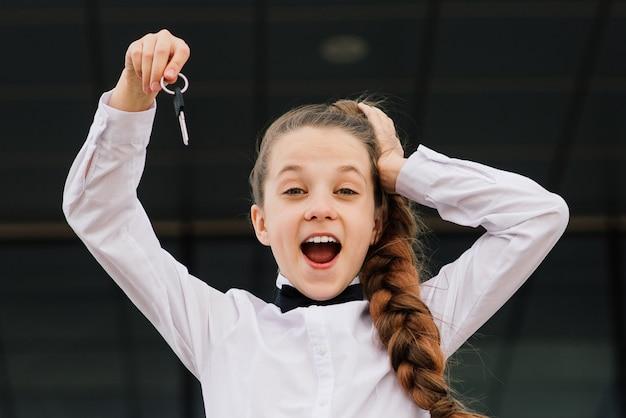 Linda garota caucasiana segurando as chaves do carro, apartamento. dia livre do carro mundial.