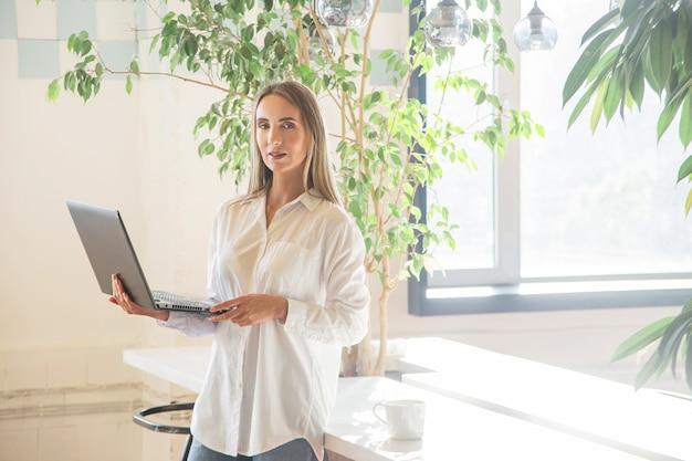 Linda garota caucasiana, segurando um laptop nas mãos no escritório.