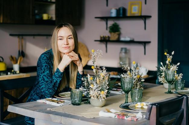Linda garota caucasiana senta-se na cozinha e pensa
